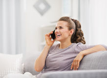 Happy young housewife talking cell phone in living room Stock Image