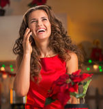 Happy young housewife talking phone in christmas kitchen Royalty Free Stock Photography
