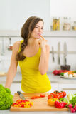 Happy young housewife tasting vegetables while cutting Royalty Free Stock Photos