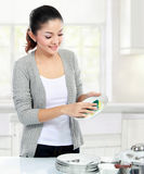 Housewife washing dishes. Happy Young housewife Washing Dishes in the kitchen Royalty Free Stock Photos