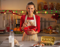 Happy young housewife whisking dough in kitchen Royalty Free Stock Image