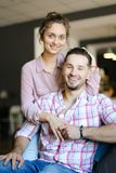 Happy young husband sitting with wife at home. royalty free stock photo