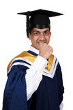 Happy young Indian graduate. Celebrating with clenched fist and wearing blue gown and square academic cap; isolated on white background Stock Photo