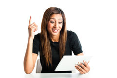 Happy young indian teen girl on tablet computer. Attractive young asian indian teenage woman, working with a portable tablet computer looking happy and pointing Royalty Free Stock Photography