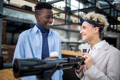 Business development. Happy young intercultural colleagues standing by telescope and discussing development of new kinds of business Royalty Free Stock Image