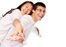 Happy young interracial couple posing as flying. Laughing young interracial couple in love having fun posing as flying isolated on white background Royalty Free Stock Photography
