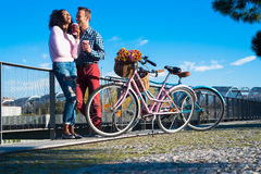 Happy young interracial couple by the river with their vintage b Stock Photos