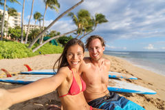 Happy young interracial couple taking phone selfie. Picture relaxing sitting near surfboards on beach holiday having fun doing surfing activity class. Travel royalty free stock image