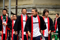 Happy young Japanese men in traditional clothes