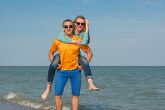 Happy young joyful guy and girl. Having fun on the beach, laughing together. During summer holidays vacation on sea. Beautiful energetic couple friends Royalty Free Stock Image