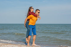 Happy young joyful guy and girl. Having fun on the beach, laughing together. During summer holidays vacation on sea. Beautiful energetic couple friends Stock Image