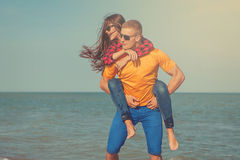Happy young joyful guy and girl. Having fun on the beach, laughing together. During summer holidays vacation on sea. Beautiful energetic couple friends Stock Photo