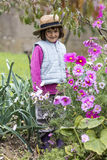 Happy young kid playing in organic vegetable and flowers garden Stock Photos