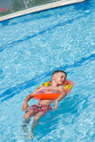 Happy young kid relaxing in a sparkling pool Stock Photography
