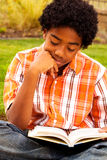 Happy young kid smiling and reading. Royalty Free Stock Photos