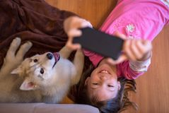Happy young kid taking a selfie with her husky dog puppy stock image
