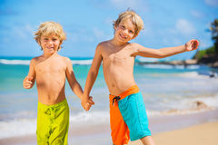 Happy young kids playing at the beach on summer vacation Stock Images