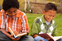 Happy young kids smiling and reading. Royalty Free Stock Images