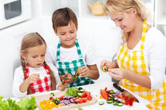 Happy young kids with their mother in the kitchen, top view clos Stock Images