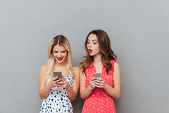 Happy young ladies chatting by phone. Royalty Free Stock Images