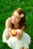Happy young lady with beautiful sappy apple. Adorable happy young lady with beautiful sappy apple over green grass Stock Image
