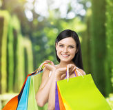 A happy young lady with the colourful shopping bags from the fancy shops. A concept of a walking in the park after the shopping royalty free stock photography