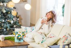 Happy young lady with curly hair sits near the Christmas tree stock image