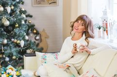 Happy young lady with curly hair sits near the Christmas tree royalty free stock image