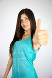 Happy young lady with freckles and long shiny hair thumb up Stock Photography
