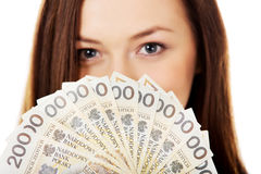 Happy young lady holding cash-polish zloty Royalty Free Stock Photos