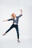 Happy young lady holding phone while jumping. Image of happy young lady holding phone  on a white background while jumping Royalty Free Stock Images