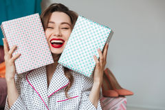 Happy young lady indoors with gift boxes. Stock Image