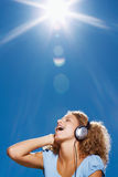 Happy young lady listening to music outdoors Stock Photography