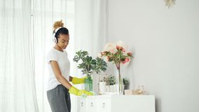 Happy young lady is listening to music through headphones and dancing during clean-up in modern studio, girl is holding. Happy young lady is listening to music stock video