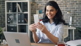 Happy young lady making video call with smartphone from office sending air kiss. Happy young lady is making online video call with smartphone from office talking stock video