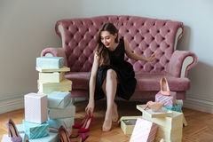 Happy young lady sitting on sofa choosing shoes. Royalty Free Stock Image