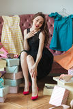Happy young lady sitting on sofa indoors choosing shoes Royalty Free Stock Photography
