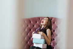 Happy young lady sitting on sofa indoors choosing shoes Stock Photos