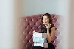 Happy young lady sitting on sofa indoors choosing shoes Stock Photo