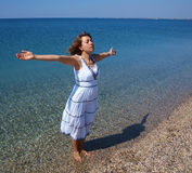 Happy young lady standing on a coastline Royalty Free Stock Images