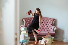 Happy young lady standing near sofa indoors choosing shoes Stock Photo