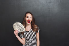 Happy young lady standing over grey wall and holding money Stock Photography