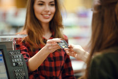 Happy young lady standing in supermarket shop holding credit card. Stock Photography