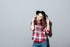 Happy young lady talking by phone. Image of happy young lady standing over grey wall wearing hat talking by phone. Looking at camera Royalty Free Stock Photo