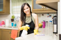Young woman doing housework, cleaning the kitchen. Happy young latin woman cleaning kitchen counter Royalty Free Stock Photography