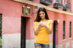Happy young latin woman talking and texting on smart phone. Wearing casual clothes sitting in with a take away coffee in a urban bench royalty free stock photography