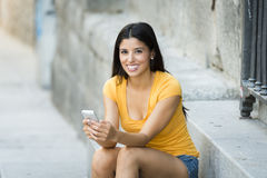 Happy young latin woman talking and texting on smart phone Royalty Free Stock Photography