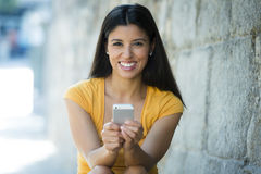 Happy young latin woman talking and texting on smart phone Royalty Free Stock Photos