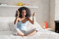 Happy Woman Smiling For Joy With Pregnancy Test Kit. Happy young latina woman holding pregnancy test kit, waiting for result. Euphoric hispanic girl smiling for stock image