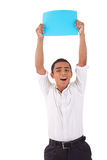 Happy young latino man, raised arms with blue card Stock Photos